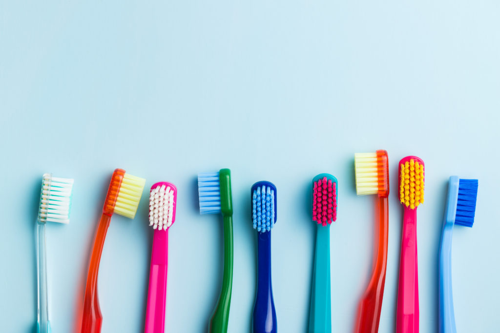 Colorful toothbrushes on blue background. Top view.